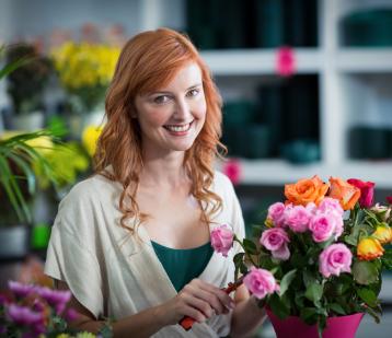 Ekspedientka rozpakowuje zaopatrzenie kwiaciarni